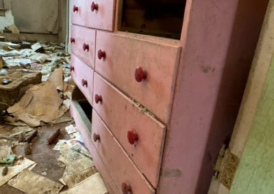 pink dresser in an abandoned farmhouse