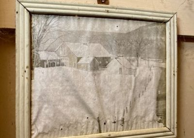 picture hanging in an abandoned farmhouse