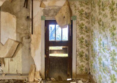 abandoned farmhouse living room front door green wallpaper