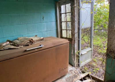 abandoned rusted freezer in a farmhouse