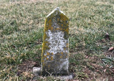 abandoned cemetery in ohio with small pointed tombstone