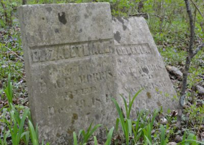 two headstones in an abandoned cemetery
