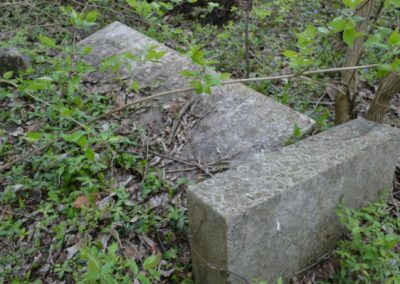 two rectangle headstones in an abandoned cemetery