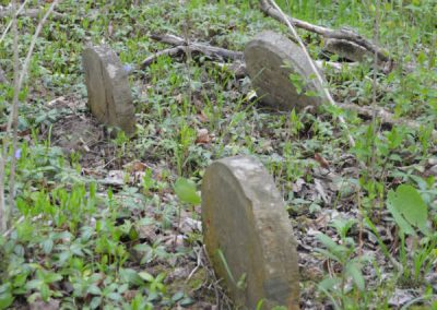 three round abandoned headstones in the woods