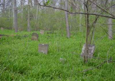 abandoned cemetery in the woods with headstones