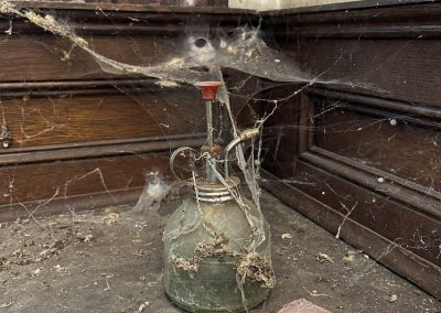 abandoned bottle covered in spider webs dust