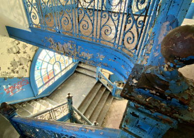 abandoned school blue staircase round window