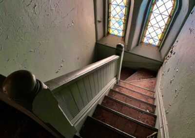 abandoned-church-staircase-two-stained-glass-windows