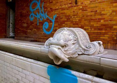 serpent head sculpture in pool abandoned school