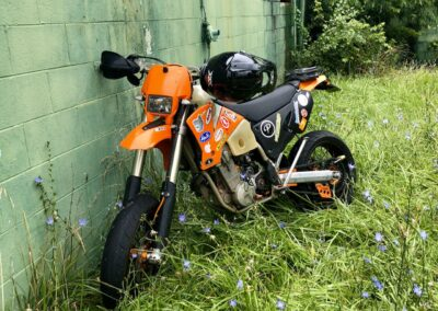 supermoto-in-thick-grass-against-abandoned-building